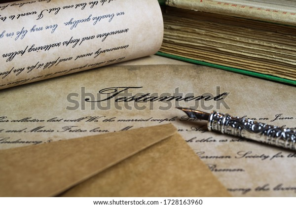 Viersen, Germany - May .6. 2020: Macro closeup of retro ink pen, old vintage paper with handwritten text for last will testament (focus on word testament in center, text and documents are self made)