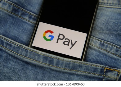 Viersen, Germany - May 9. 2020: Close up of isolated mobile phone with payment provider Google pay logo lettering in jeans pocket (focus on letter P)