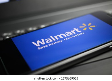Viersen, Germany - May 9. 2020: Close up of mobile phone with walmart online trader logo lettering on computer keyboard (selective focus on big letter L)