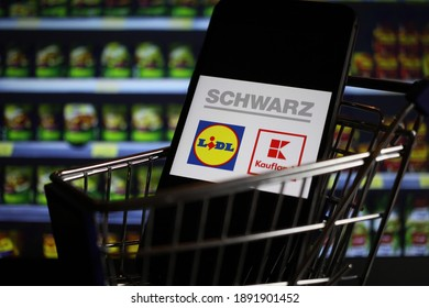 Viersen, Germany - May 9. 2020: Close up of mobile phone screen in shopping cart modell with logo lettering of german Schwarz group supermarket chain (focus on center of lidl logo)