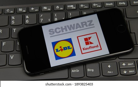 Viersen, Germany - May 9. 2020: Closeup of mobile phone on laptop keyboard with logo lettering of german Schwarz group (focus on lidl logo)