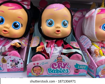 Viersen, Germany - October 8. 2020: Close up of IMC toys cry babies dolls in shelf of german supermarket (focus on face of central doll