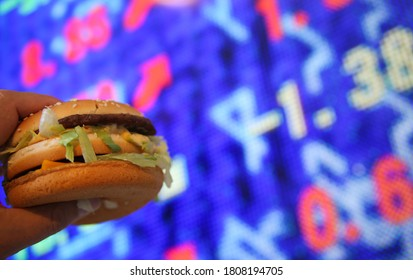 Viersen, July 9. 2020: View on hand holding big mac burger in front of stock market chart board  - index and mcdonalds goodwill ranking  value company assets concept