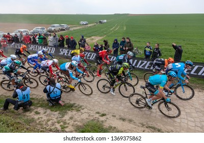 Viesly, France - April 14, 2019: Bird eye view of the peloton riding on the cobblestone road from Briastre to Viesly during Paris Roubaix 2019.