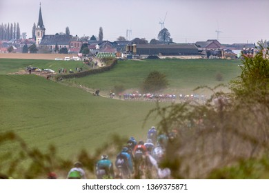 Viesly, France - April 14, 2019: The peloton riding on the cobblestone road from Briastre to Viesly during Paris Roubaix 2019.
