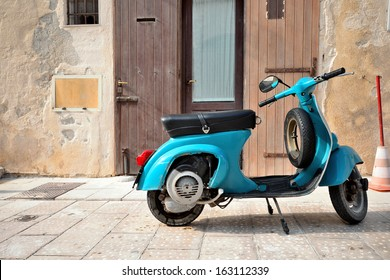 VIESTE, ITALY - August 23: Blue vintage Vespa in old street in medieval center of Vieste, August 23, 2013 Vieste, Italy. This is the preferred way to travel in old narrow streets of Vieste