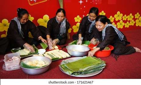 VIET NAM- JAN 15: Group of people with traditional Vietnamese dress (ao ba ba) and bandanna making traditional food- cylindric rice cake ( banh Tet) for Tet ( Lunar New Year) in Vietnam, Jan 15, 2013