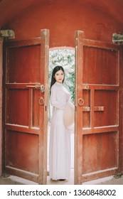 Vietnam beautiful girl wearing traditional Ao Dai and Non La in Hue citadel.