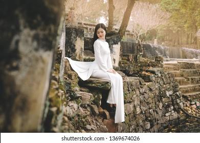 Vietnam beautiful girl wearing traditional Ao Dai and Non La in Hue citadel