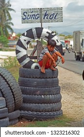 VIETNAM, DA LAT – MAY 15, 2002: young boy relaxing on truck tires station. Country typical place.