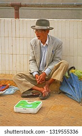 VIETNAM, DA LAT – MAY 20, 2002: guy offering a scale for people weighting in the city center. The place has a great humanity.