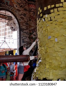 VIETNAM, DALAT - MARCH 25, 2018: A young woman glues a note with desires for a bell of wishes in Pagoda Fucock.