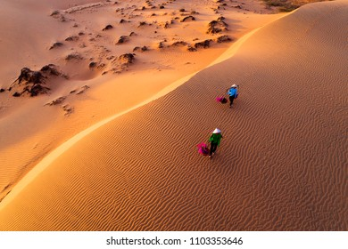 Vietnam Dec2017: aerial view of Woman carrying flower basket at sunset in Mui Ne sand dune, Vietnam