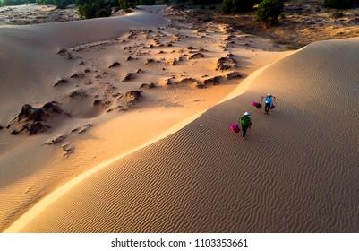 Vietnam Dec2017: aerial view of Woman carrying flower basket at sunset in Mui Ne sand dune, Vietnam