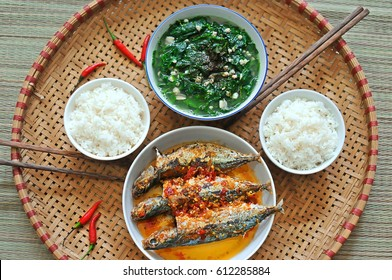 Vietnam family lunch set for two person: cooked rice, vegetable soup and fried fishes.
