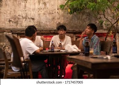 Vietnam; Feb 2020: Group of three young men smoking and drinking Tiger beer at a bar, vintage hipster atmosphere, before Covid-19 coronavirus crisis. Ho Chi Minh city, Saigon, Vietnam, Southeast Asia