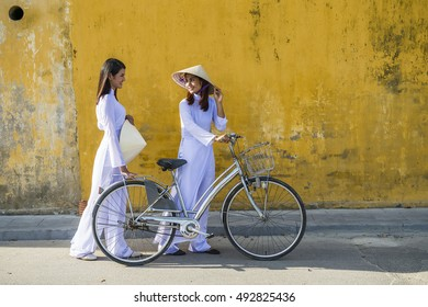 Vietnam girls with a vietnamese traditional costume wearing Ao dai ride a bicycle at Hua. Many vietnam woman in hue city still wearing traditional dress.Hue is old town and many history building