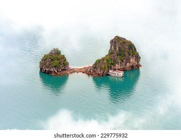 Vietnam Halong Bay cruise boat near tropical island. Aerial photo view of mountain in sea near Hanoi - adventure travel landscape background