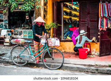 VIETNAM, HANOI - FEBRUARY 14, 2017:  A Vietnamese woman in a traditional hat on a bicycle is standing behind a souvenir shop on the streets of the old city of Hoi An.