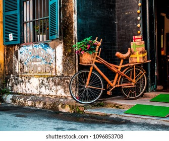 VIETNAM, HANOI - FEBRUARY 14, 2017: The old restaurant and architecture in Hoi An, near the wall an orange bike with a basket in front decorated with plants.