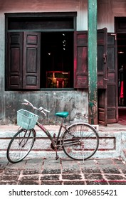 VIETNAM, HANOI - FEBRUARY 14, 2017: An old restaurant with dark windows and blue piles in the city of Hoi An. A parked bicycle near the entrance with a blue basket.