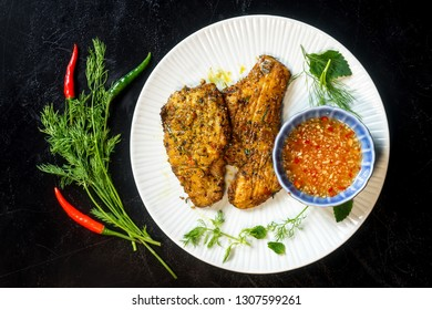 Vietnam, Hanoi grilled turmeric fish with dill (Cha ca La vong) and fish sauce garnished with chili and dill on black background