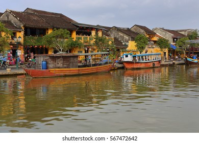Vietnam, Hoi An - January 2017: Pleasure boat floats on Bon River against the backdrop of houses on the waterfront in the town of Hoi An