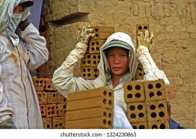 VIETNAM, HOI AN – MAY 20, 2001: young lady operating in the city brick furnace. Many young girls work in the furnace.