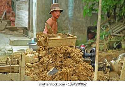 VIETNAM, HOI AN – MAY 20, 2001: guy operating the machine to create the bricks. Many young persons work in the furnace.