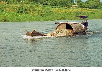 VIETNAM, HUE – JULY 15, 2002:  boat carrying sand on the Perfume river. The boat is very typical and  colorful.