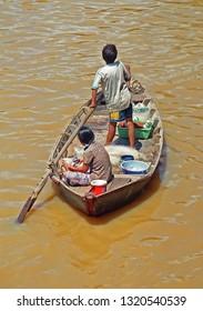 VIETNAM, MUI NE – JANUARY 15, 2001: man and woman managing a fishing boat. A village typical scene.