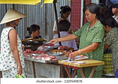 VIETNAM, MUI NE – JANUARY 15, 2001: lady selling meats in the open market. The place has a great humanity.