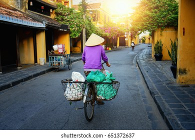 Vietnam people,Vietnamese ride bicycle on during sunrise,woman with Vietnam culture traditional,Morning view of busy street in Hoi An, Hoi An is the World's Cultural heritage site ,Hoi an, Vietnam