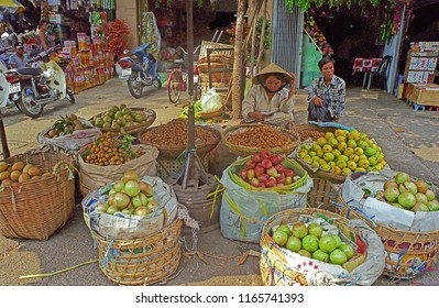 VIETNAM, SAIGON – FEBRUARY 20, 2001: lady selling rose apple, Syzygium jambos and pomelo fruits in Ben Thanh district open market. The place has a great humanity.