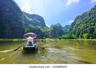 VIETNAM ; TAM COC 23-3-18;unidentified tourists are traveling in boat along the Ngo Dong River and taking picture of the Tam Coc, Rower using feet to propel oars. Tam coc