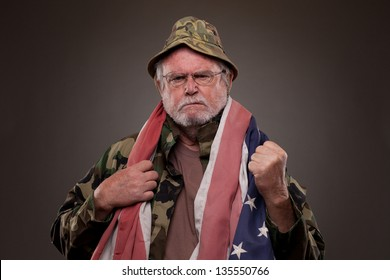 Vietnam Veteran with American flag around his neck showing his fist