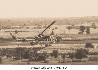 Vietnam War 'style' image of helicopters flying low over the jungle soldiers shot machine guns from the aircraft. vintage style (Artist's Impression)