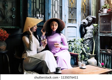 Vietnam woman wearing Ao Dai culture traditional drinking coffee at Ho Chi Minh in Vietnam,vintage style,travel and relaxing concept.