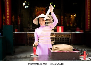 Vietnam woman wearing Ao Dai culture traditional dress praying with incense stick in the burning pot of the Chinese temple, Ho Chi Minh Vietnam.