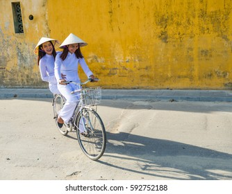 Vietnam women ride a bicycle who wearing Ao dai. It's a vietnamese national costume. Many people hope to preserved vietnamese culture. You can see from many city Ex. hue, hoi an and danang