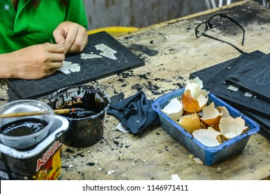 Vietnamese artist is making sea shell and egg shell lacquered picture at a craft center owned by Vietnamese government, Ho Chi Minh City, July 2018