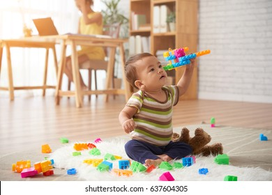 Vietnamese baby boy playing with plastic blocks