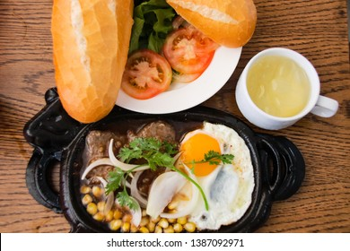 Vietnamese breakfast of baguette (banh mi), tea, beef with gravy (Bo ne pate) and corned beef with egg (trung op la)