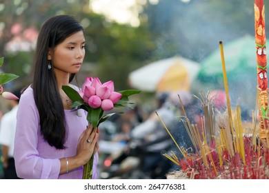 Vietnamese Buddhist woman praying at temple holding lotus flower bud bunch