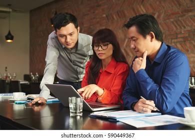 Vietnamese business partners reading data on laptop screen