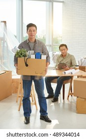 Vietnamese businessman with big cardboard box of belongings