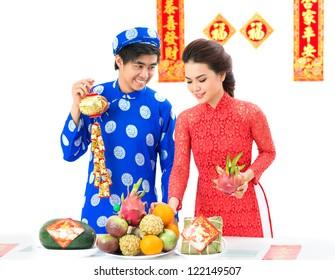 Vietnamese couple decorating festive table for Tet