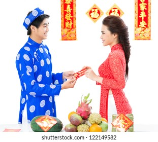 Vietnamese couple exchanging red envelopes for Tet