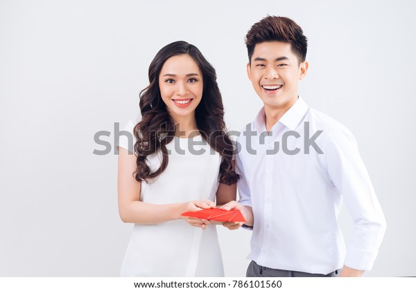 Vietnamese couple exchanging red lucky money envelopes. Tet holiday.