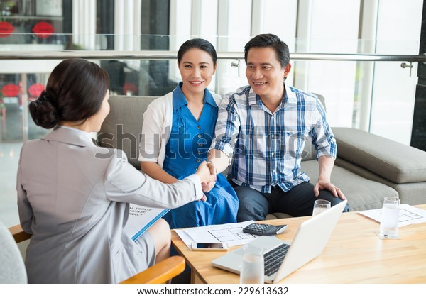 Vietnamese couple greeting estate agent